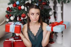niña en una bata verde sosteniendo dos cajas de regalo, qué regalo elegir foto
