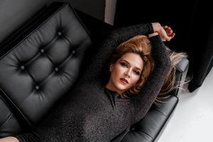 hermosa chica en vestido negro se acuesta en el sofá foto