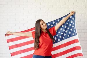 Beautiful young woman with American flag, arms outstretched photo