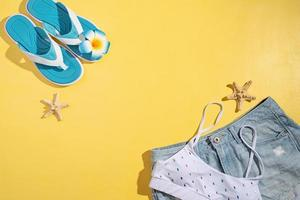 Summer accessories with clothes, shoes, tropical leaves and flowers photo