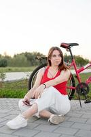 Girl sitting next to her bike in the park listening to the music photo