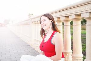 Girl sitting next to column fencing listening to the music photo