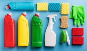 Varias botellas sanitarias y herramientas de limpieza sobre fondo azul. foto