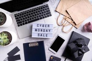 Cyber monday sale text on lightbox, top view of workspace flat lay photo