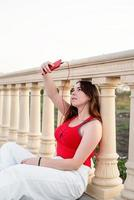 Girl sitting next to column making selfie and listening to the music photo