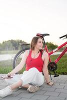 Girl sitting next to her bike listening to the music in the park photo