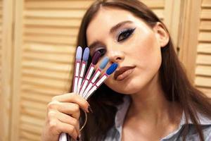 chica con maquillaje azul cubre su rostro con una paleta con uñas foto