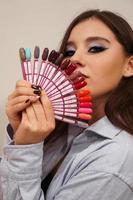hermosa niña cubre su rostro con una paleta con uñas foto