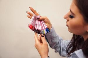 la niña elige el color del esmalte para manicura. probadores de uñas foto