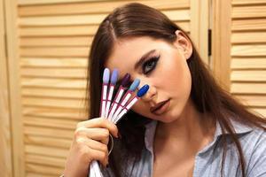 Hermosa chica con maquillaje azul cubre su rostro con una paleta de uñas foto