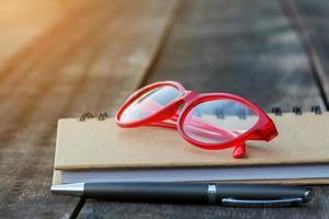 Gafas rojas en el cuaderno con bolígrafo y fondo de madera foto