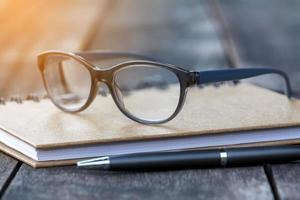 Gafas en cuaderno con bolígrafo y fondo de madera foto