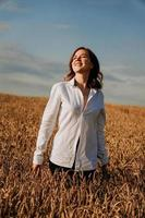 Happy young woman in a white shirt in a wheat field. Sunny day. photo