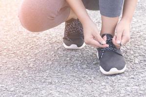 Woman tying shoes photo