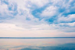 Multicolored clouds in the blue sky over the sea photo