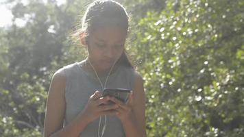 fille utilisant un téléphone portable avec des écouteurs en forêt sous la lumière du soleil video