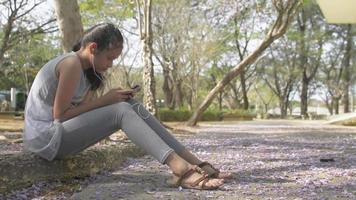 linda garota sentada no parque usando telefone celular com fones de ouvido video