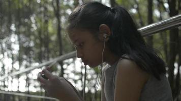 fille utilisant un téléphone portable avec des écouteurs et assise dans le parc video