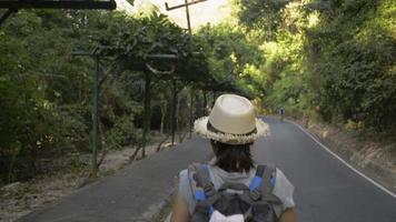 vue arrière femme avec sac à dos descendant de la colline video