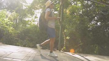 femme avec sac à dos marche sur un sentier descendant de la colline video