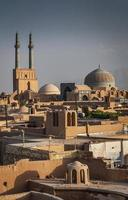 Rooftops downtown mosque and landscape view of Yazd city old town in Iran photo
