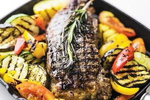 Greek organic lamb steak with grilled vegetables and herbs in sizzling skillet photo