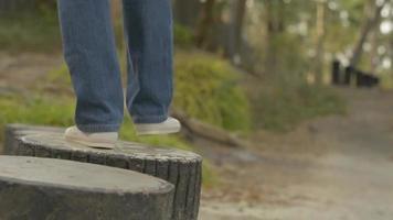 Follow shot woman legs wearing jeans walking on concrete stump video