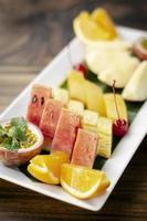 Mixed fresh cut organic fruit salad platter outdoors on wood table photo