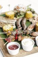 Parrillada orgánica parrillada plato de carne comida rústica con salchichas, brochetas, guarniciones y salsas foto