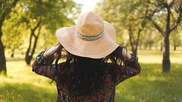 Back of beautiful hipster girl in hat and dress. Summer day photo
