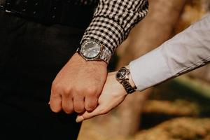 Couple of lovers holding hands. Hand with wrist watch. photo