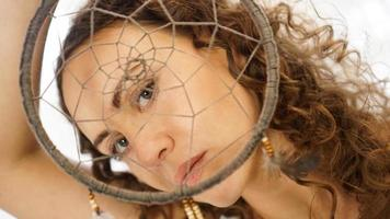 Woman with curly hair with a dream catcher in hand photo