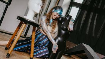 Hermosa artista de pelo largo en taller con maniquíes foto