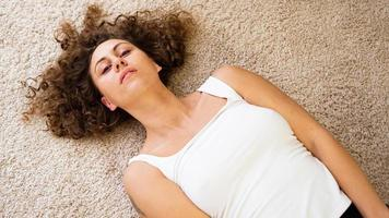 Woman Lying Down on Carpet, Happy Young Adult Girl Lie on Floor photo