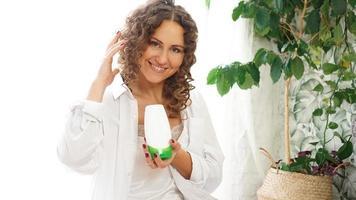 Pretty Woman mostrando tubo cosmético blanco para el cuidado del cabello rizado en la mano foto