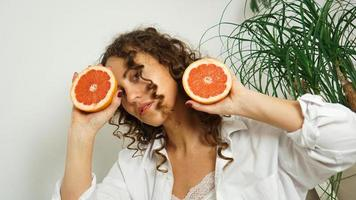 Portrait of pretty middle-aged woman with curly hair with grapefruit photo