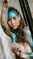 chica morena detrás de la red. mujer con destellos azules en su rostro foto