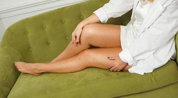 Woman with long legs on a green sofa. Health and Foot Care Concept photo