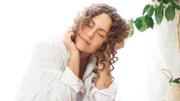 mujer sentada en casa con plantas y sonriendo a la cámara foto