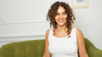 Happy young woman with curly hair in white t-shirt at home photo