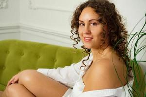 Happy young woman with curly hair in white shirt at home photo