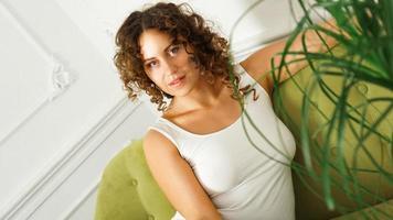 feliz, mujer joven, con, pelo rizado, en, camiseta blanca, en casa foto