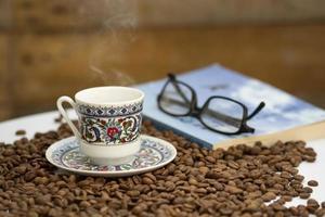 granos de café, taza de café turco y un soporte para libros sobre la mesa foto
