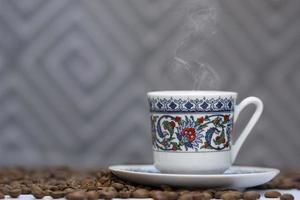 A cup of turkish coffee among the coffee grains photo