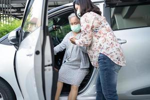 Help and support asian senior woman patient prepare get to her car photo