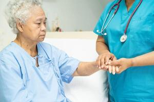 Tocar paciente mujer senior asiática con amor foto