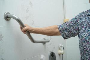 Asian senior woman patient use handle security in toilet photo