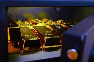 Caja fuerte de acero llena de pila de monedas y barra de oro sobre la mesa de madera foto
