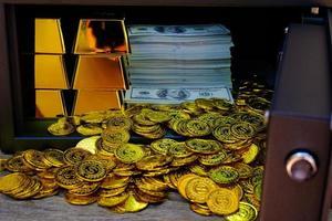 Caja fuerte de acero llena de pila de monedas y barra de oro y billete de 100 usd foto