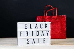 Black Friday sale. Red shopping bag and lightbox on a dark background. photo